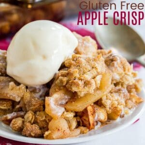a serving of gluten free apple crisp on a small plate with a scoop of vanilla ice cream on top