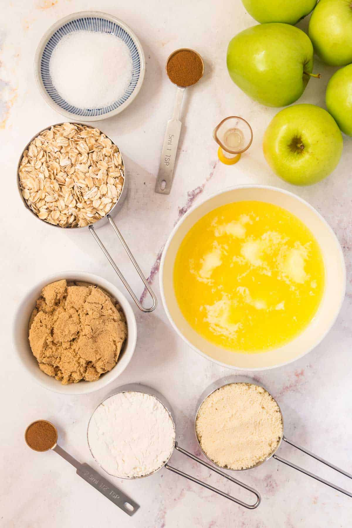 bowls of melted butter, granulated sugar, and brown sugar, two teaspoons of cinnamon, and measuring cups full of oats, almond flour, and gluten free flour, and a small beaker of lemon juice with some green apples on a marble countertop