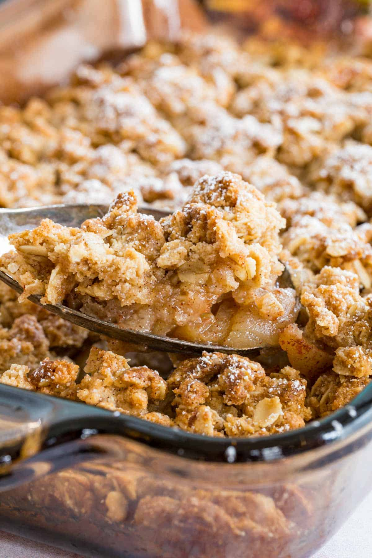 serving spoon scooping up gluten free apple crisp out of a baking dish