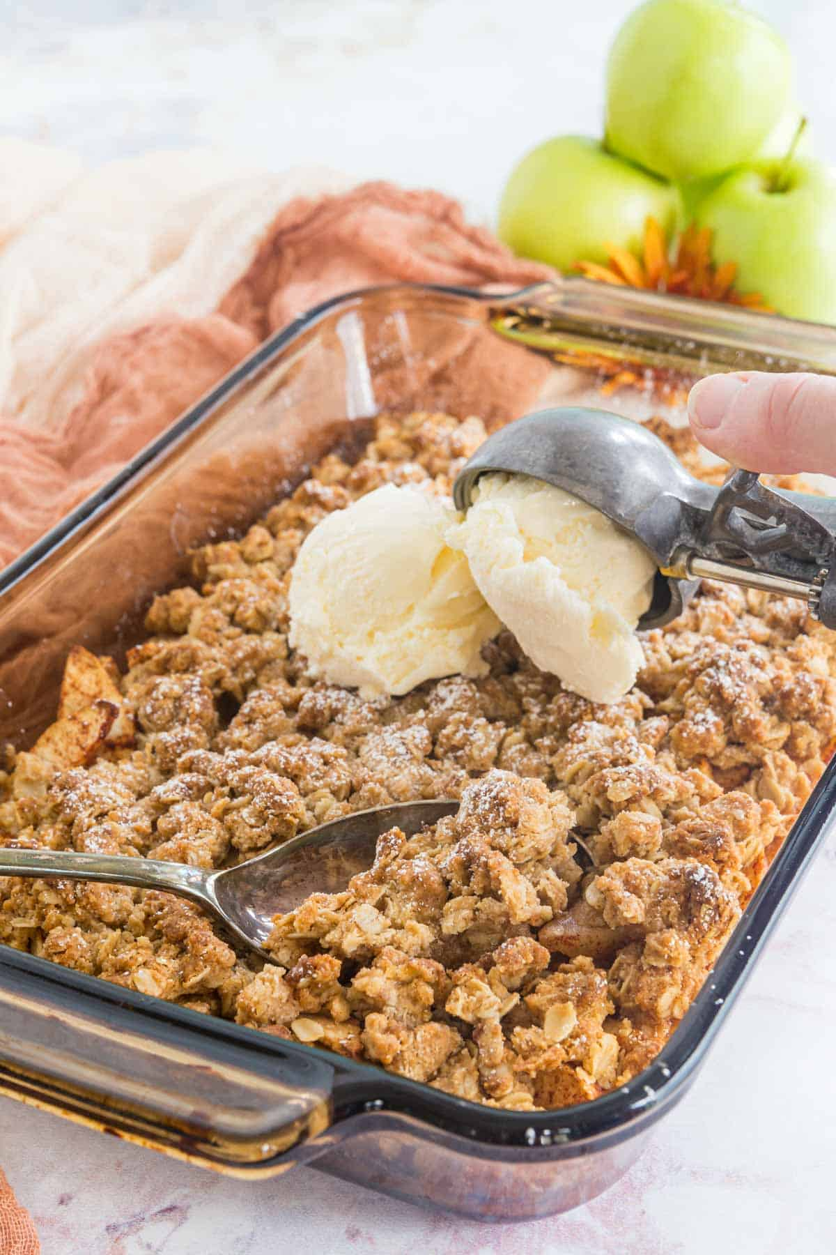 serving spoon resting in a baking dish of apple crisp with a scoops of ice cream being added on top