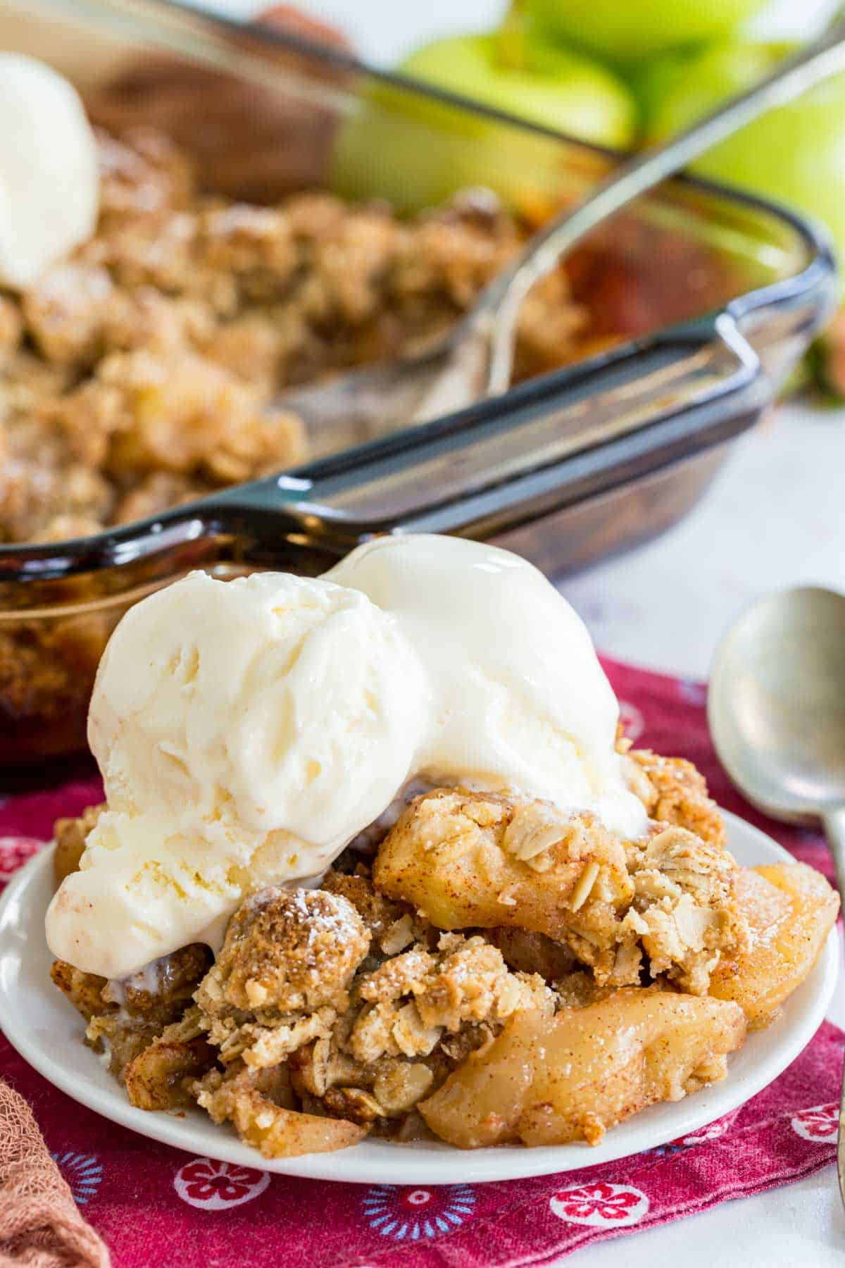 apple crisp served on a small white plate with two scoops of vanilla ice cream on top