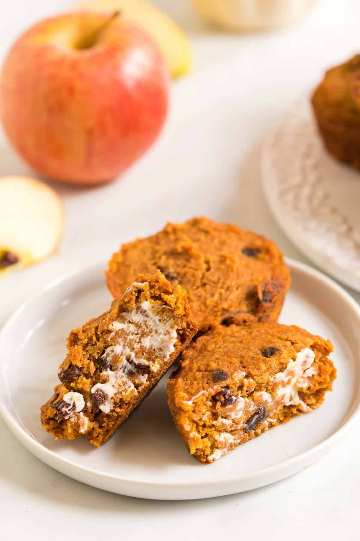 two pumpkin apple muffins with raisins on a plate with one cut in half and spread with butter