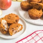 two apple pumpkin muffins with raisins on a plate with one cut in half and spread with butter next to a platter with more muffins