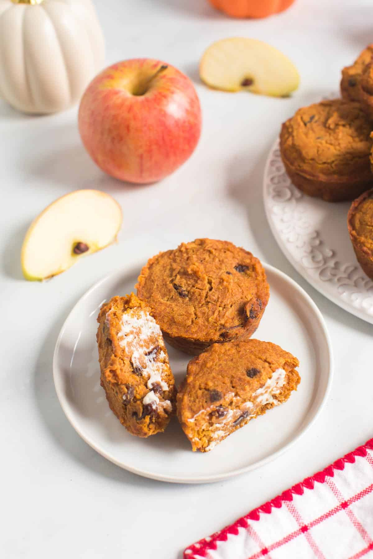 two pumpkin apple muffins with raisins on a plate with one cut in half and spread with butter next to a platter with more muffins, an apple, and some apple slices