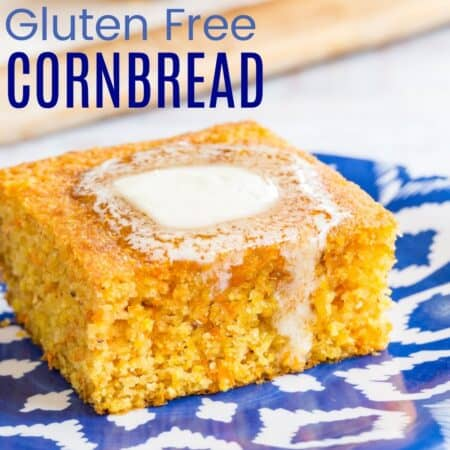 a pat of butter melting over the top of a piece of gluten free cornbread on a blue and white plate