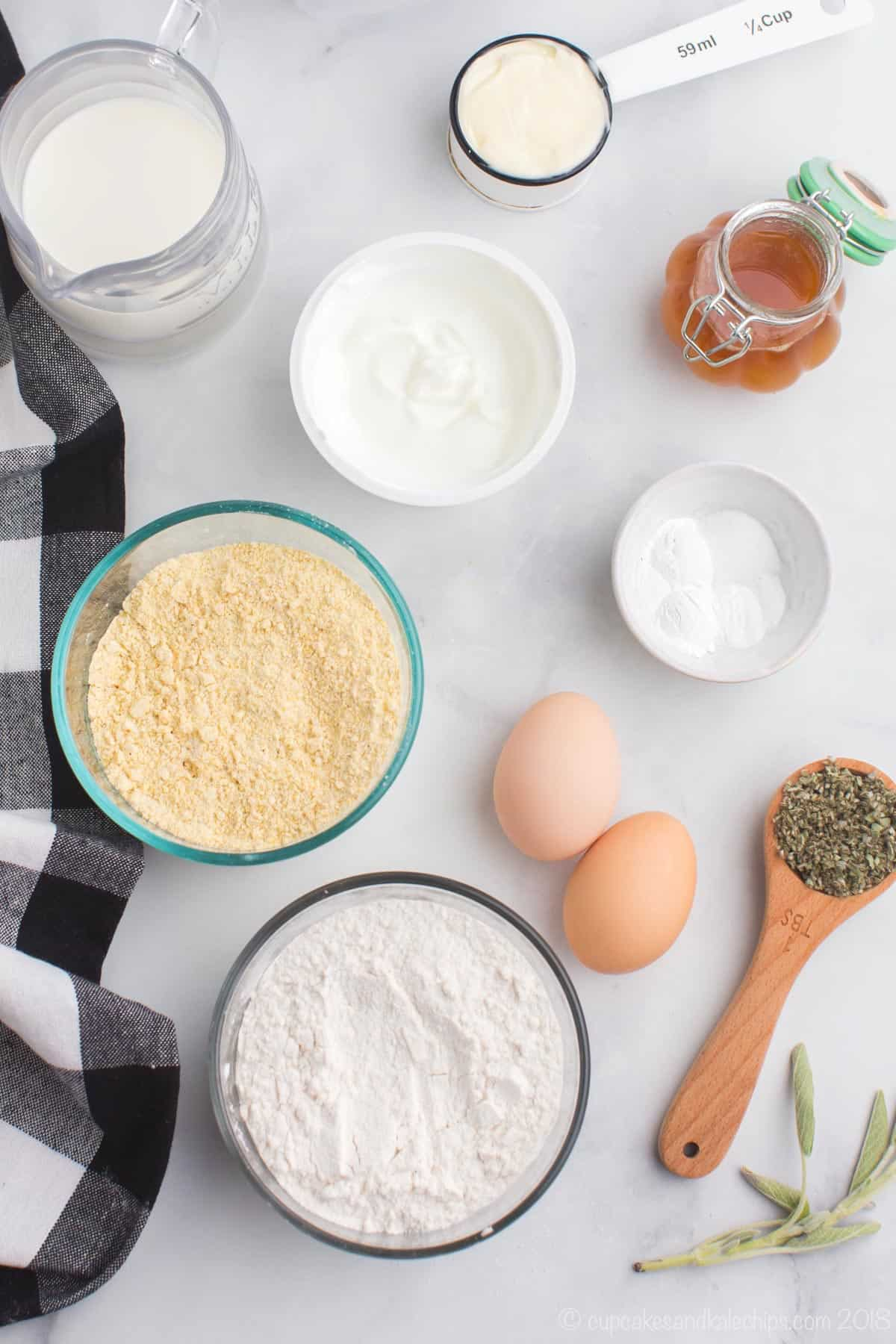 bowls of gluten free flour, cornmeal, salt, baking powder, and baking soda, a measure spoon with fresh sage, a jar of honey, two eggs, a container of yogurt, milk in a pitcher and butter in a measuring cup