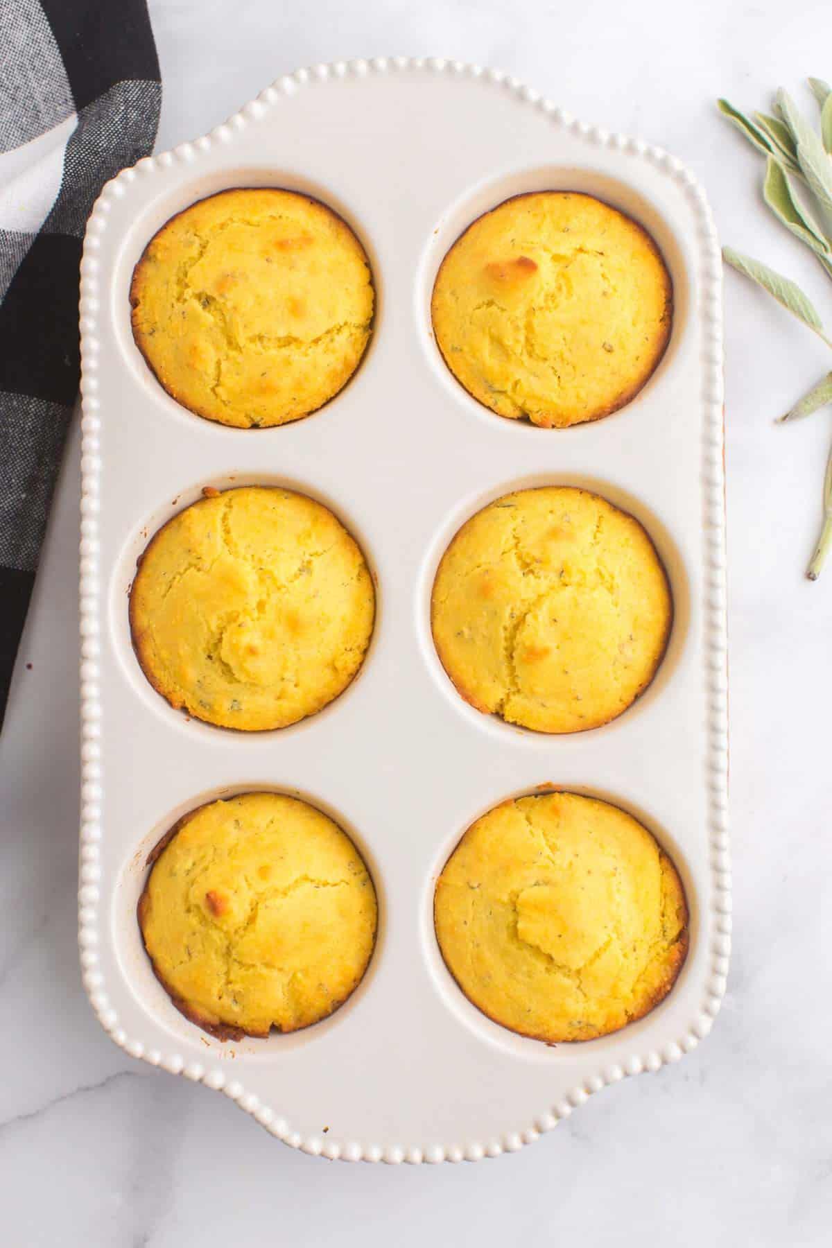 six corn muffins in a ceramic muffin pan