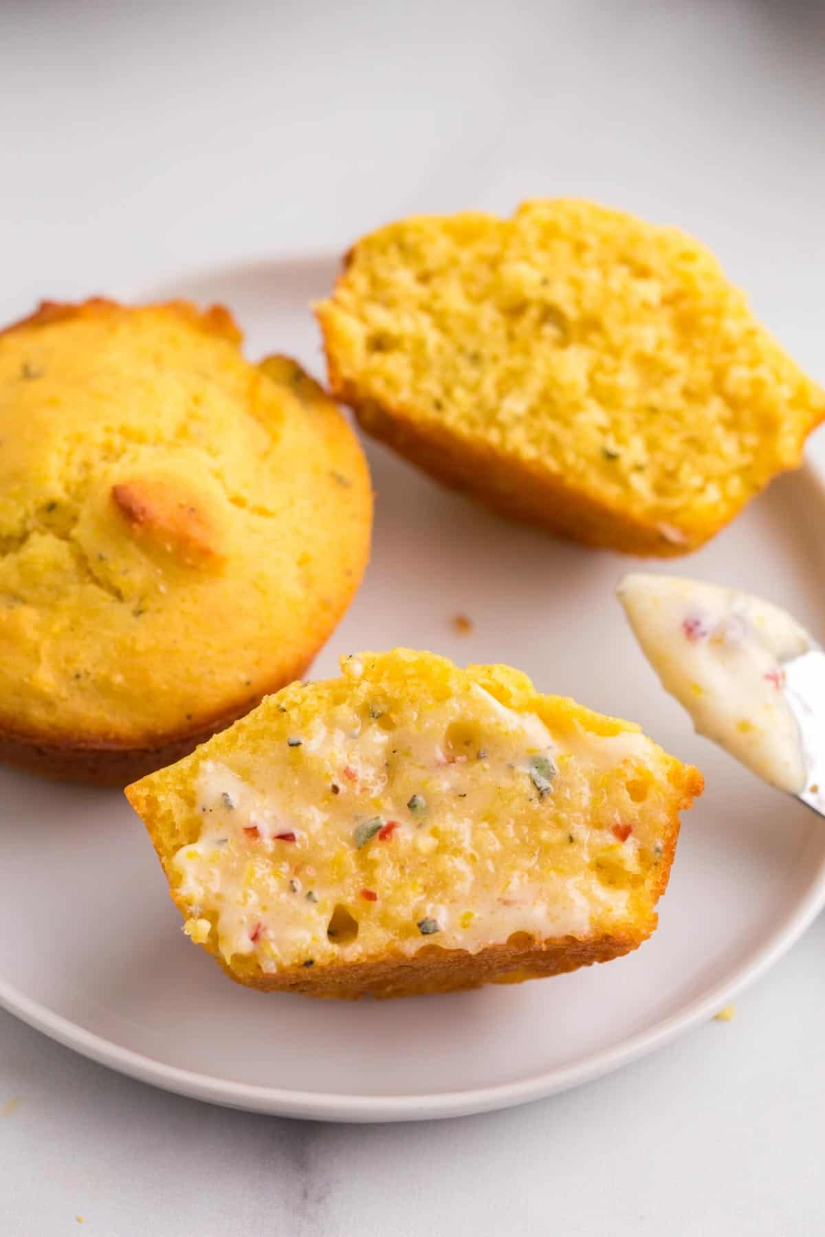 two gluten free cornbread muffins on a plate with one cut in half and one half with cranberry butter spread and melted on it