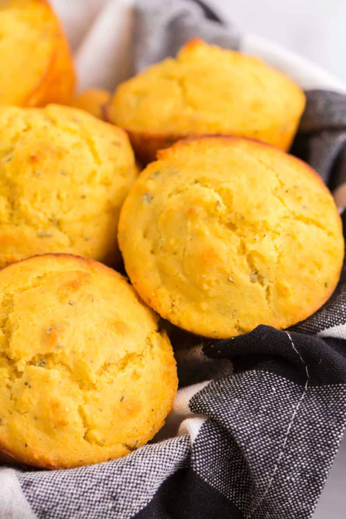 a pile of gluten free cornbread muffins in a basket lined with a black and white plaid napkin
