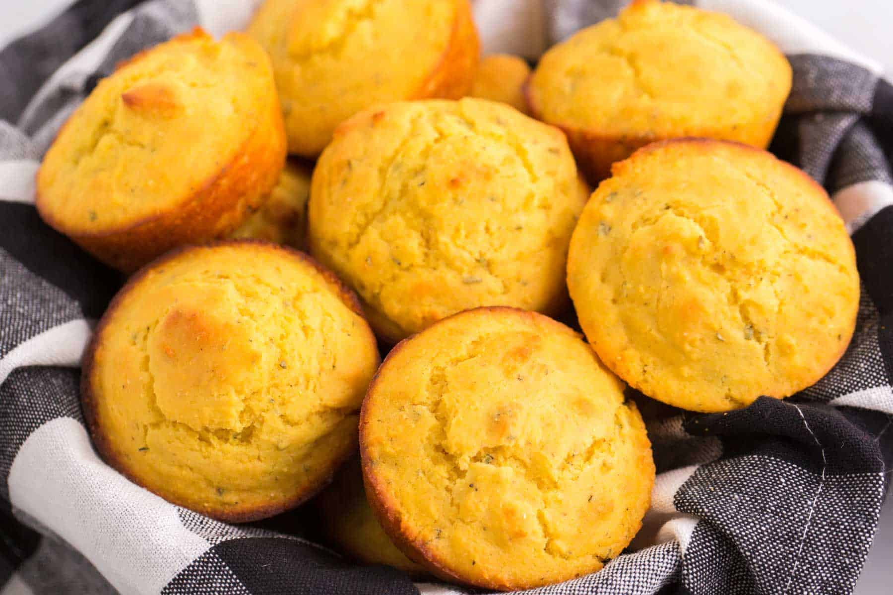 gluten free cornbread muffins in a black and white plaid cloth napkin-lined basket