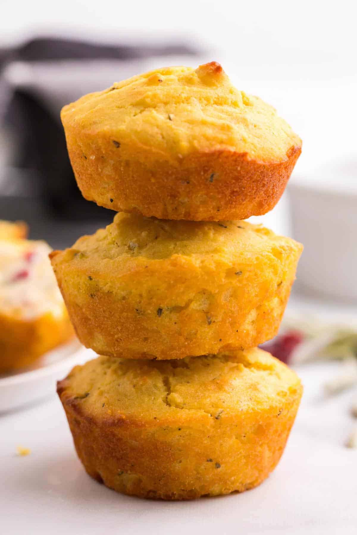three gluten free sage corn muffins stacked on top of each other