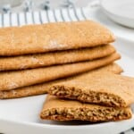 a stack of gluten free graham crackers on a plate with one broken in half on top of a striped cloth napkin