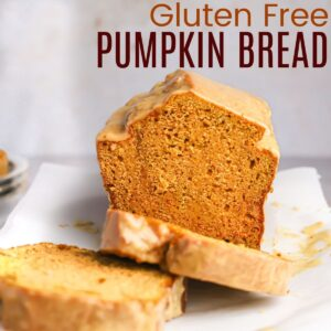 loaf of gluten free pumpkin bread on a platter with some slices lying down