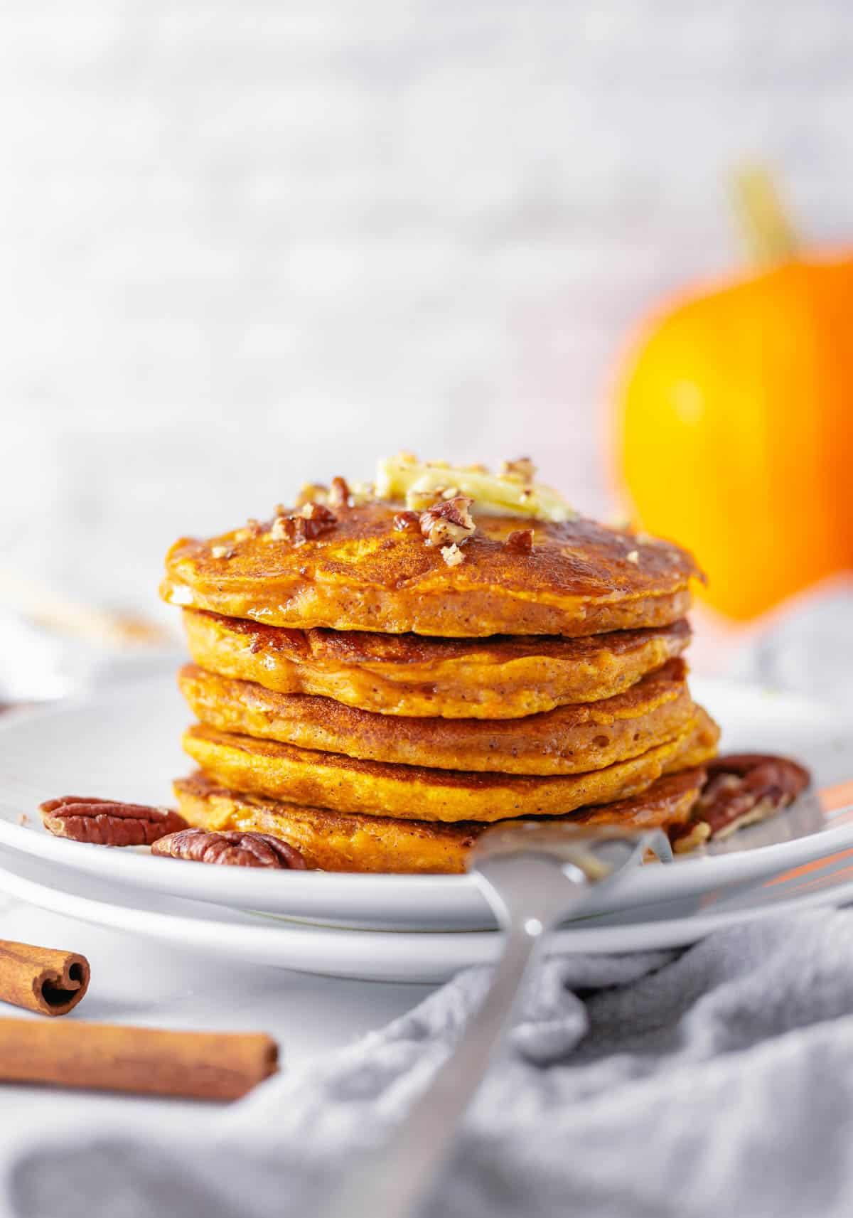 stack of gluten free pumpkin pancakes on two white plates