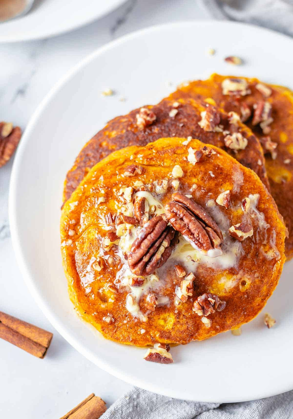 plate of pancakes with pecans on top