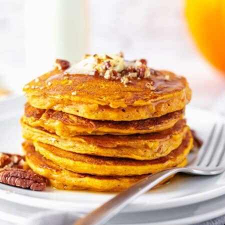 a stack of pumpkin pancakes on a plate topped with chopped pecans, butter, and syrup