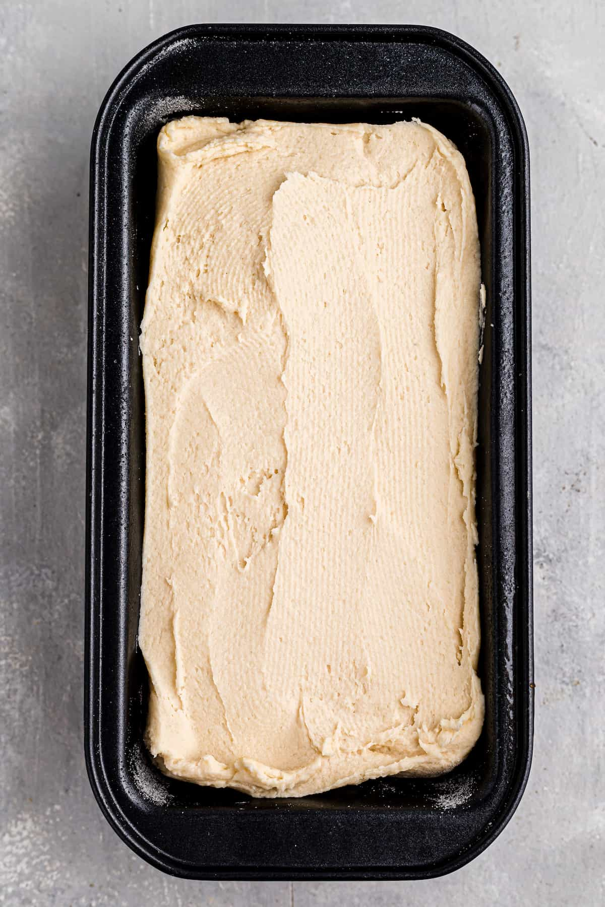 black loaf pan with bread dough