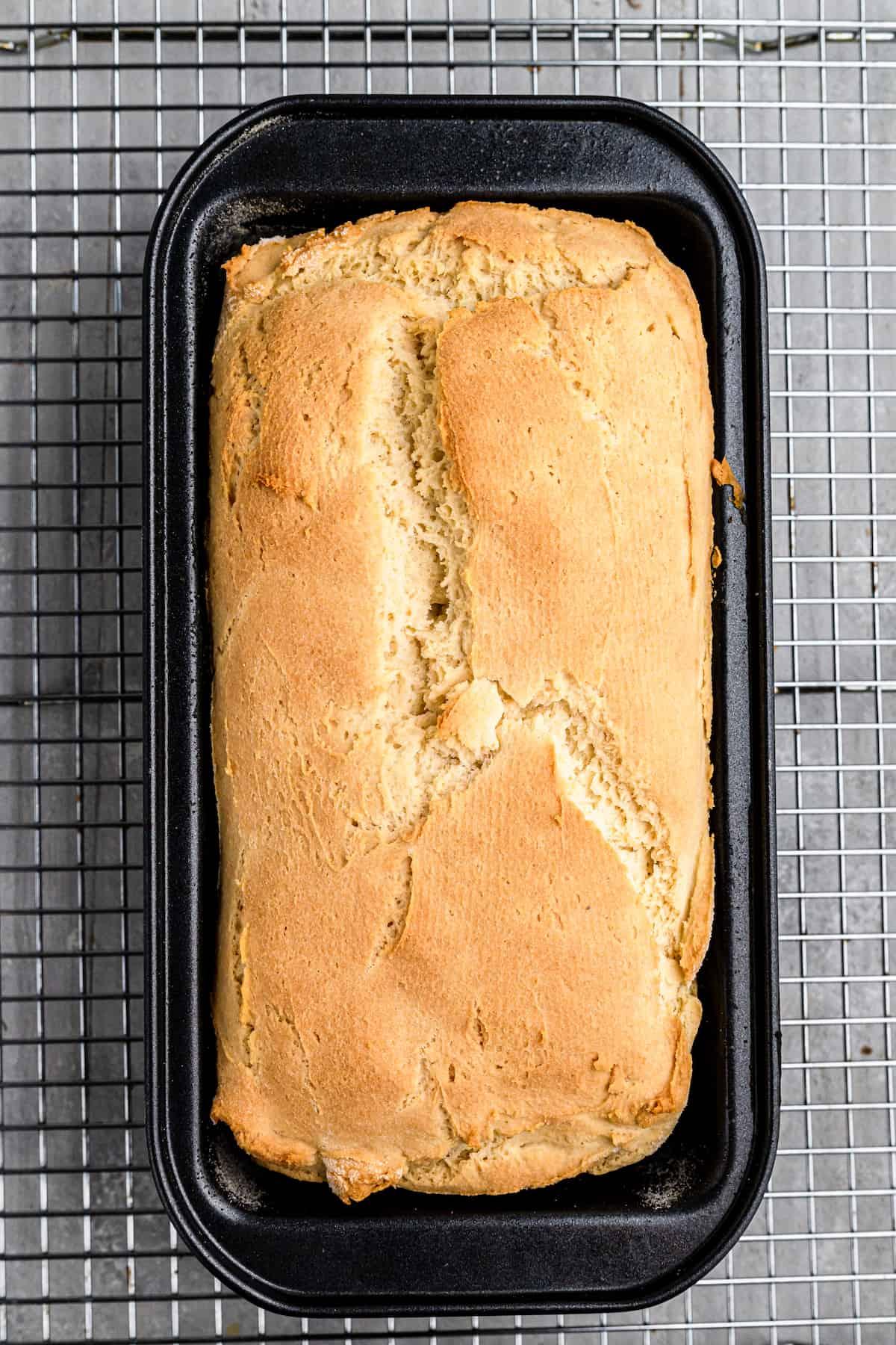 baked gluten-free sandwich bread in a loaf pan on a wire rack