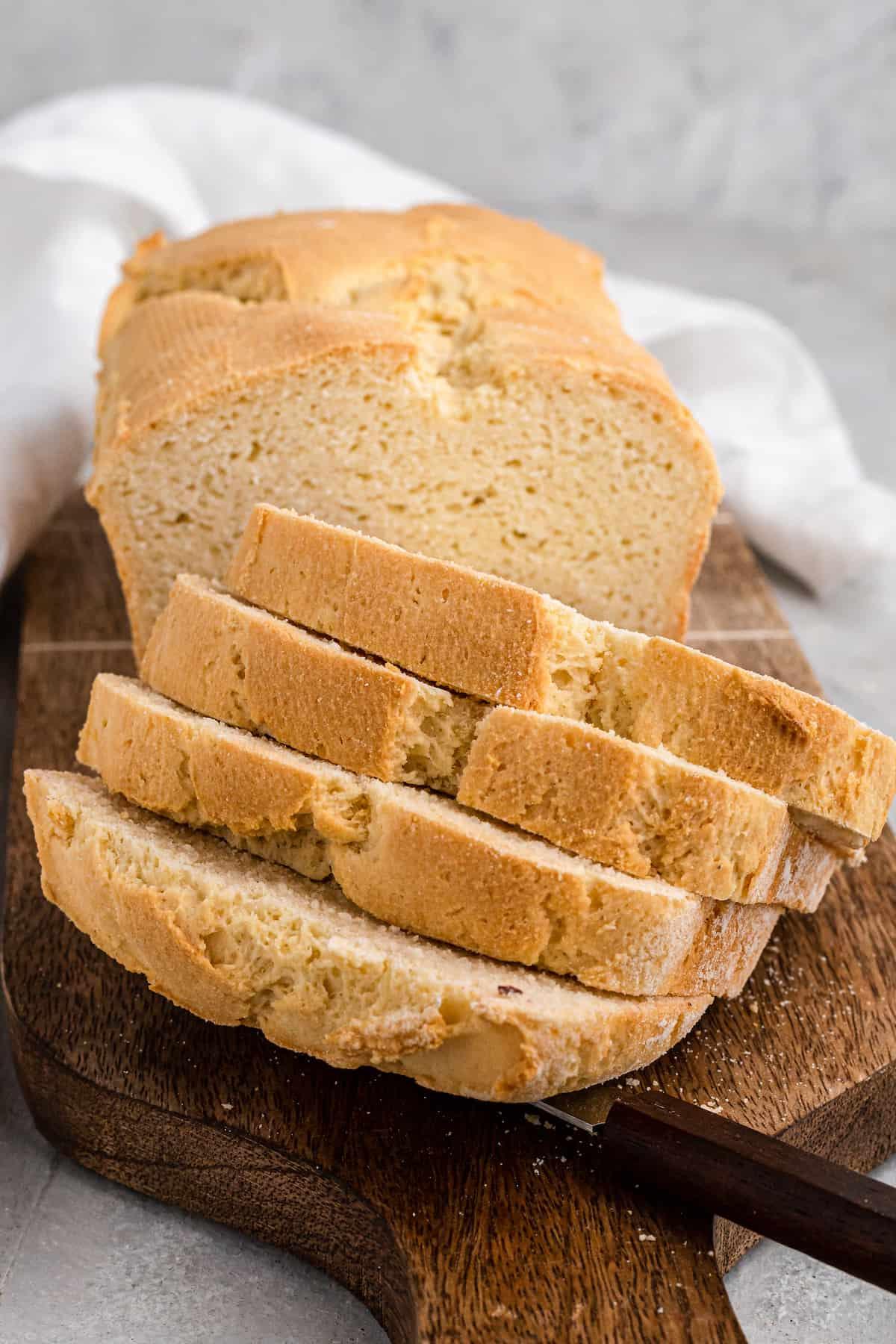 slices of stacked gluten free sandwich bread on a wooden board