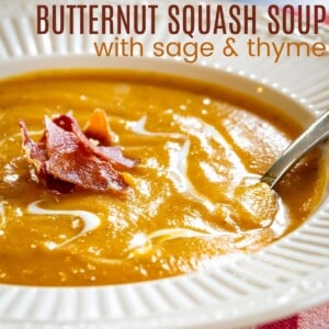spoon set in a bowl of a butternut squash soup topped with crispy bits of prosciutto