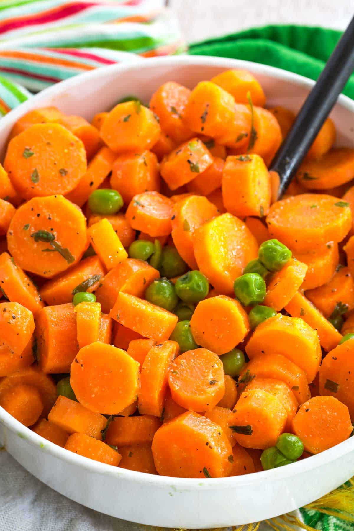 closeup of a bowl of honey dijon peas and carrots flecked with bits of parsley