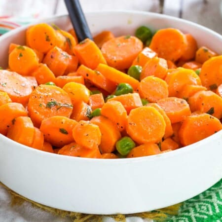 honey mustard carrots and peas in a white serving bowl