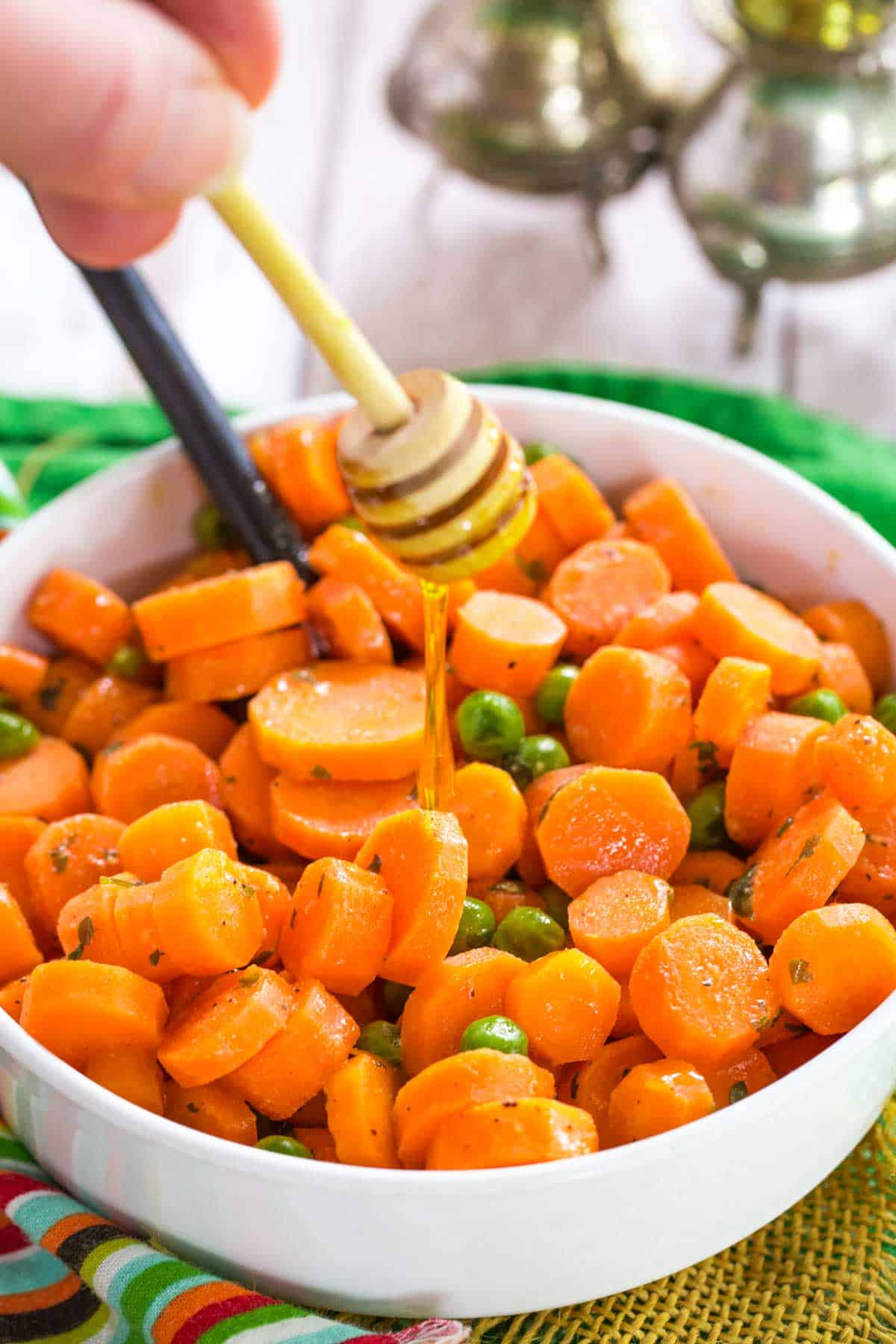 using a honey dipper to drizzle honey over a bowl of peas and carrots