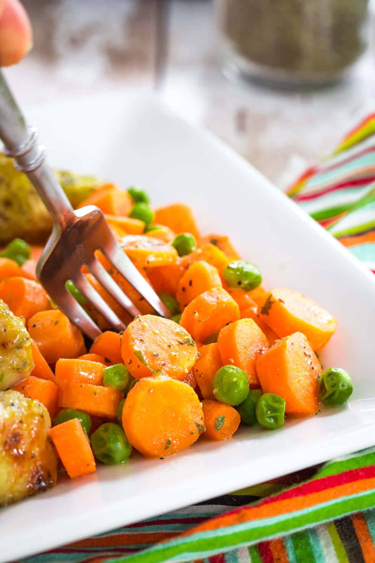 fork in a pile of carrots and peas on the edge of a white plate on top of a striped cloth napkin