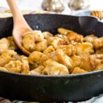 cast iron skillet on top of cloth napkins with cooked cubed chicken with a shiny glaze