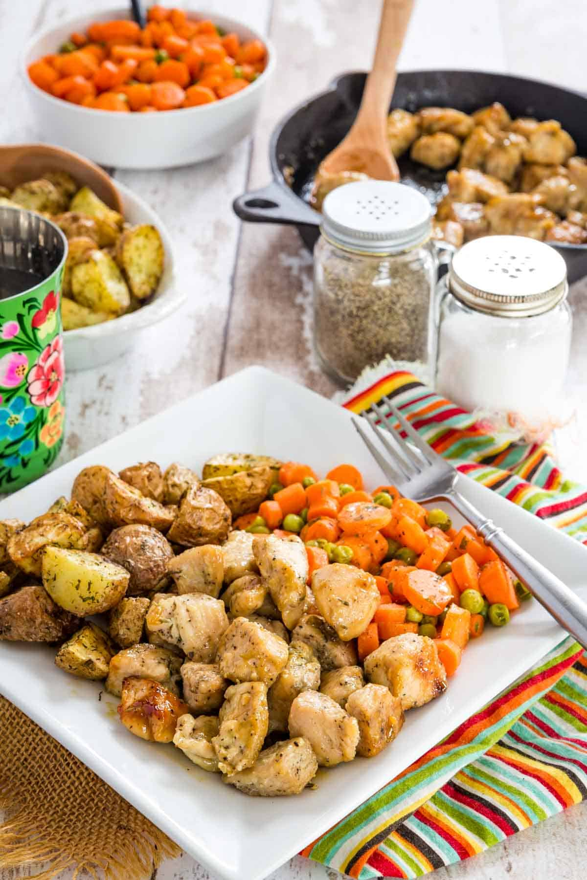 a square white plate with glazed chicken bites roasted potatoes, and peas and carrots on a table with salt and pepper shakers and each of the dishes in serving bowls