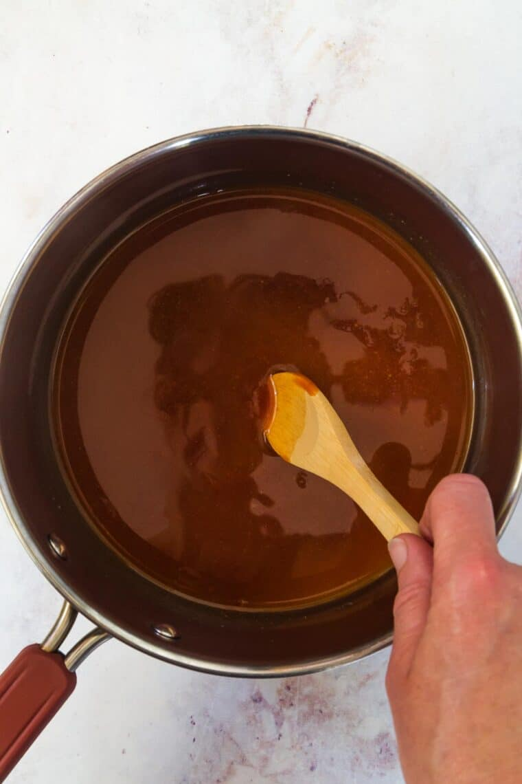 stirring barbecue sauce in a pot with a wooden spoon