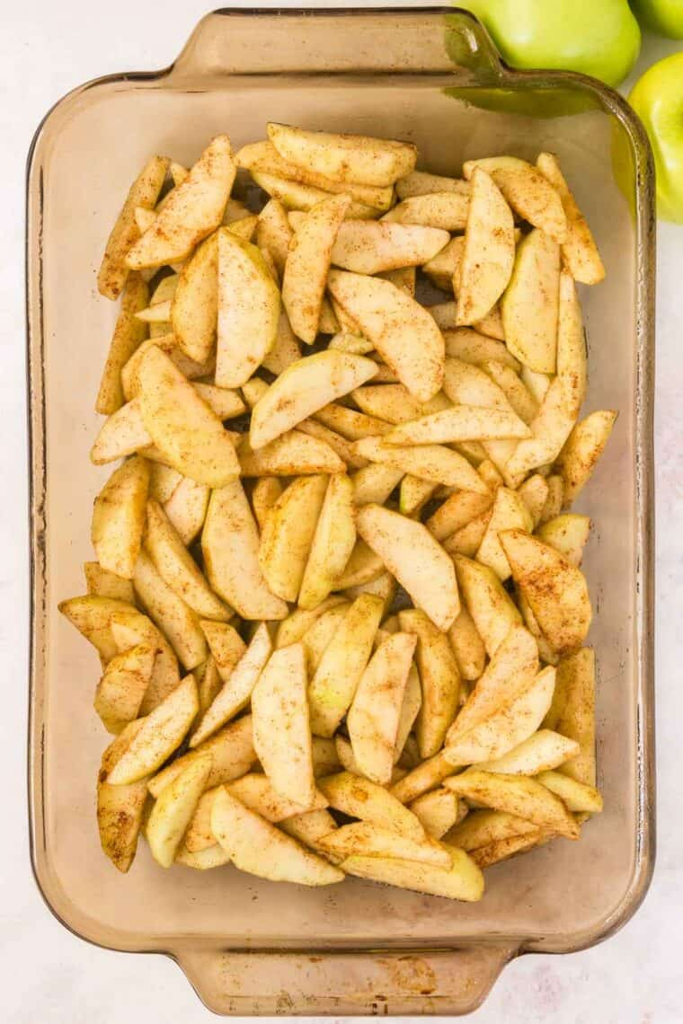 cinnamon-sugar coated apple slices in a glass baking dish
