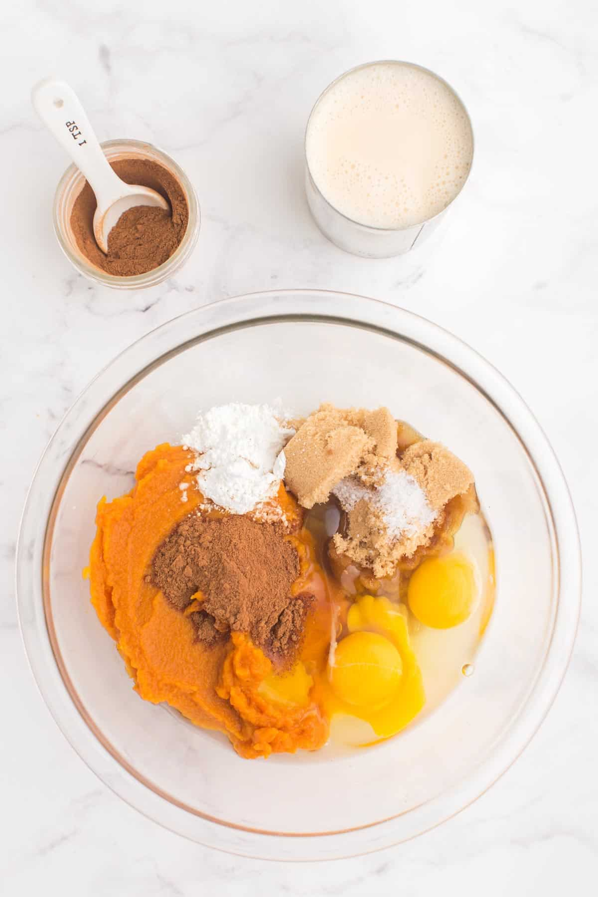 glass bowl with pumpkin puree, two eggs, light brow sugar, salt, cornstarch, and pumpkin pie spice on a marble counter top with a jar of pumpkin pie spice and a can of evaporated milk