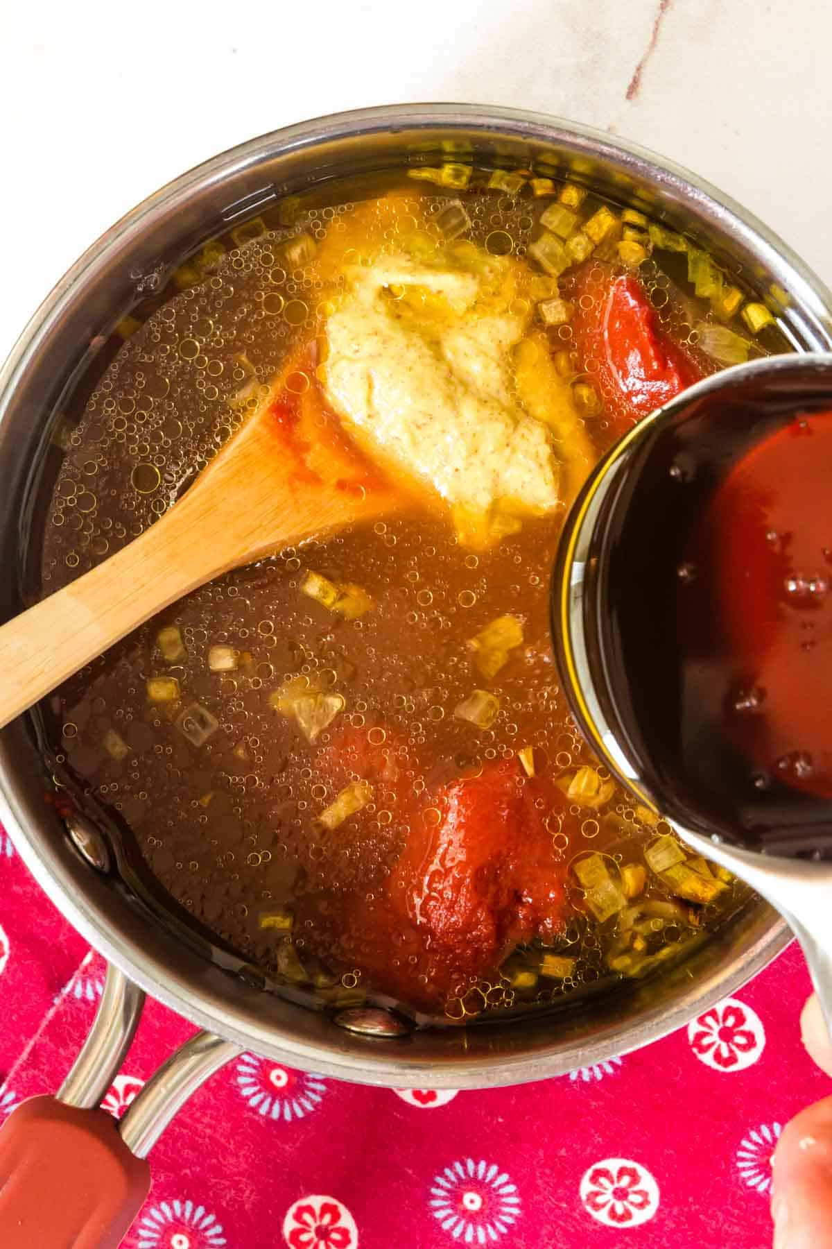 pouring honey into a saucepan with sauteed shallots, apple juice, mustard, and tomato paste