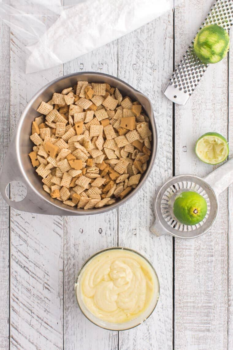 a bowl of chex and broken pieces of graham crackers, melted white chocolate, a lime on a zester and a lime on a juicer