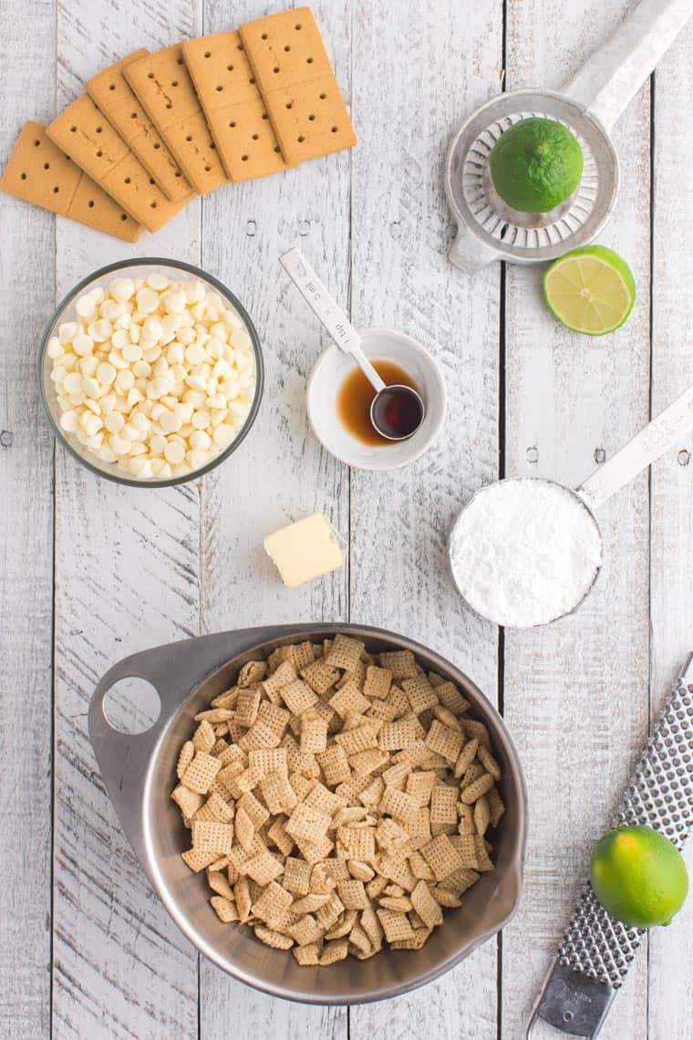 a bowl of chex cereal, a bowl of white chocolate chips, a lime with a zester and another with a juicer, graham crackers, powdered sugar in a measuring cup, vanilla, and a cube of butter