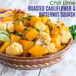 a shallow terra cotta bowl with roasted cauliflower and butternut squash