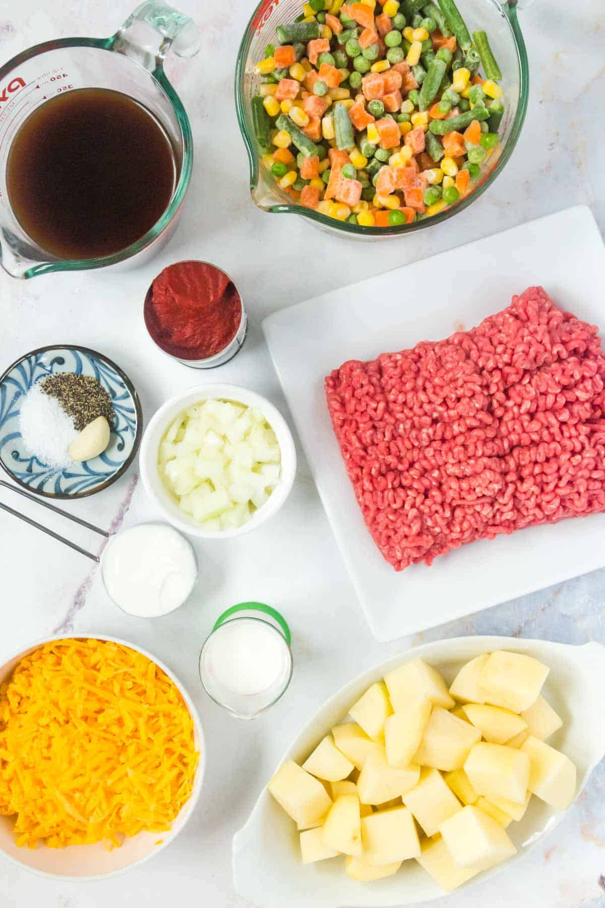Ingredients for chili in white bowls and measuring cups, including ground beef, frozen mixed vegetables, and potatoes