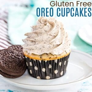 cookies and cream cupcake with frosting on a white plate with two gluten free oreos