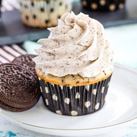 cookies and cream cupcake with frosting on a white plate with two gluten free oreos with more cupcakes on the slate platte behind it