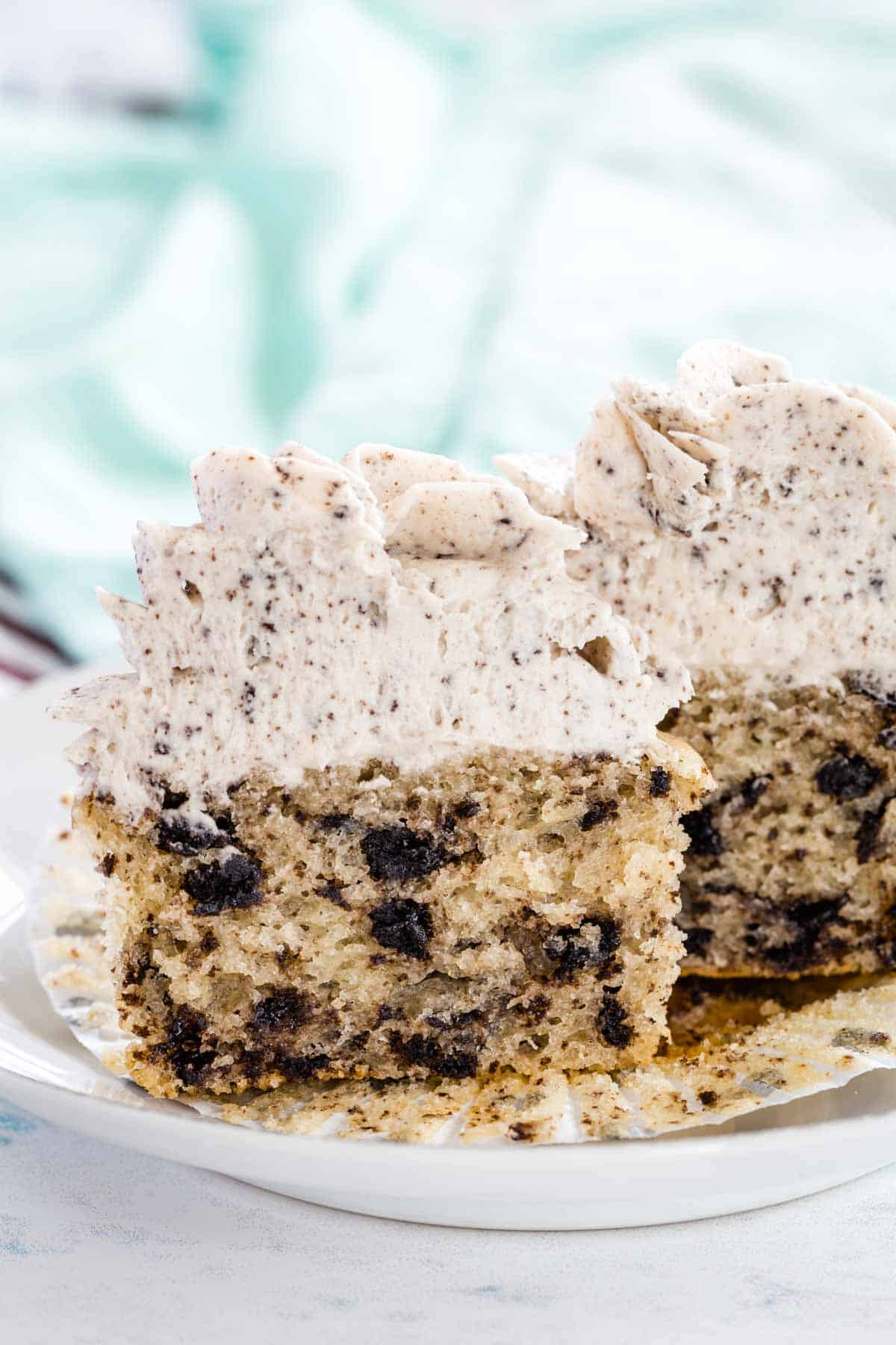 a frosted cupcake cut in half to see the oreo bits and pieces inside