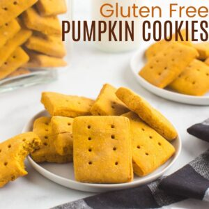 gluten free pumpkin cookies on plate with a bite taken out of one cookie nd a jar and plate of cookies in the background
