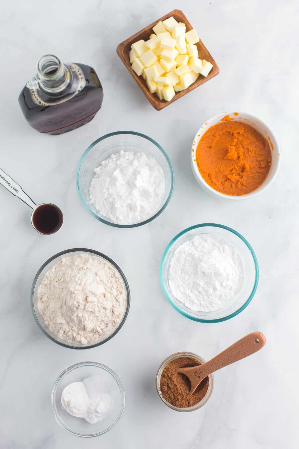 bowls of brown rice flour, tapioca starch, potato starch, salt, baking powder, baking soda, pumpkin puree, pumpkin pie spice, and cubed butter plus a bottle of maple syrup and a measuring spoon of vanilla