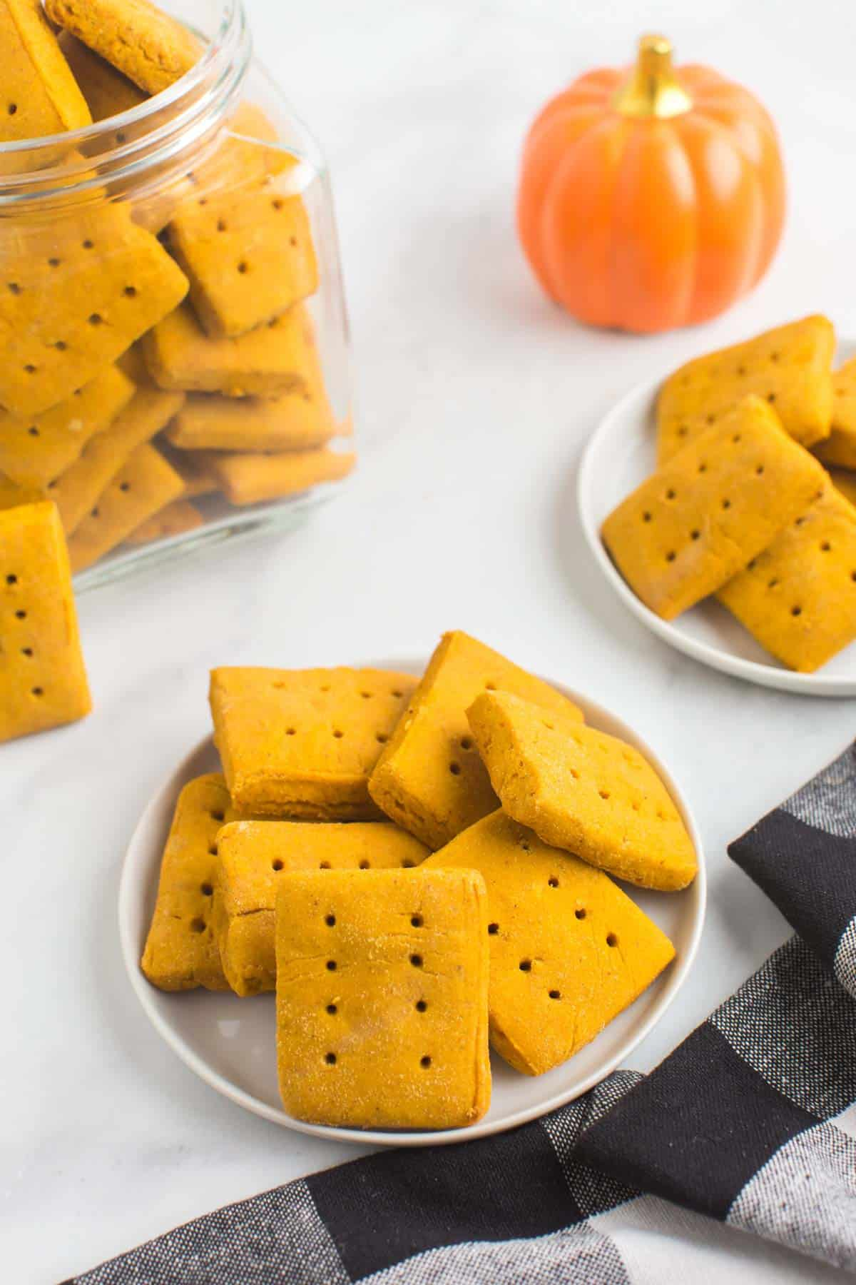 rectangluar gluten free pumpkin cookies on plates and in a jar with a black and white checked cloth napkin