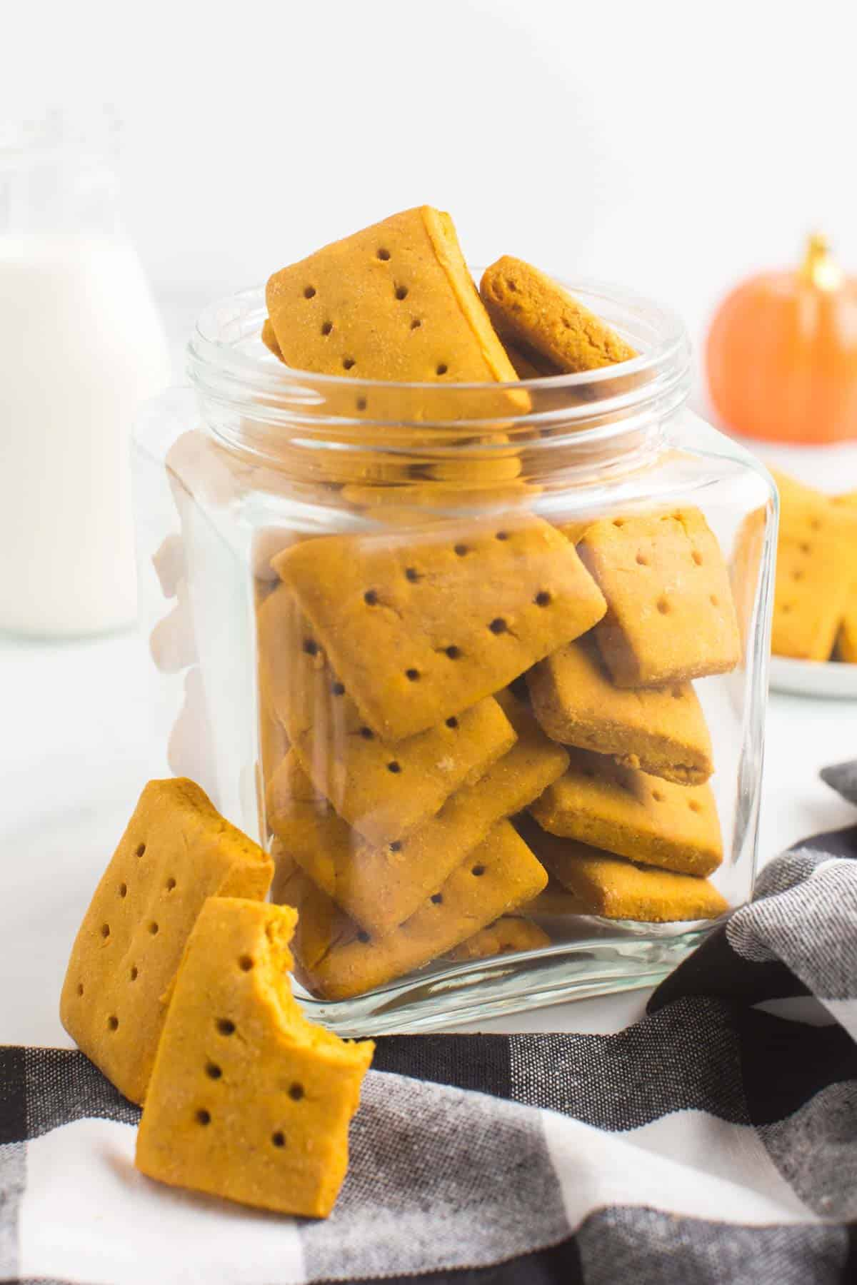 a glass jar fill of gluten free pumpkin cookies on a black and white cloth napkin with two cookies leaning against the jar