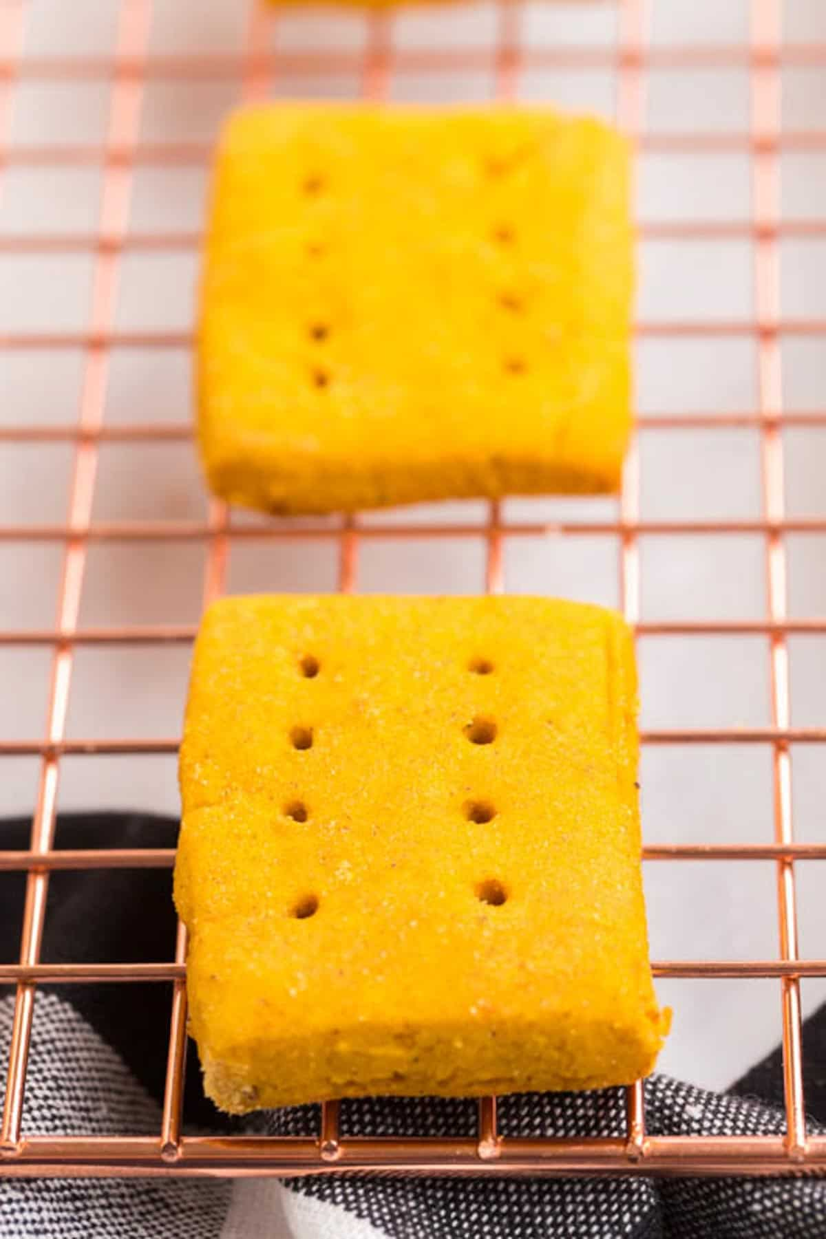closeup of a gluten free pumpkin cookie that is shaped like a rectangle and has eight small holes like graham crackers sitting on a cooling rack