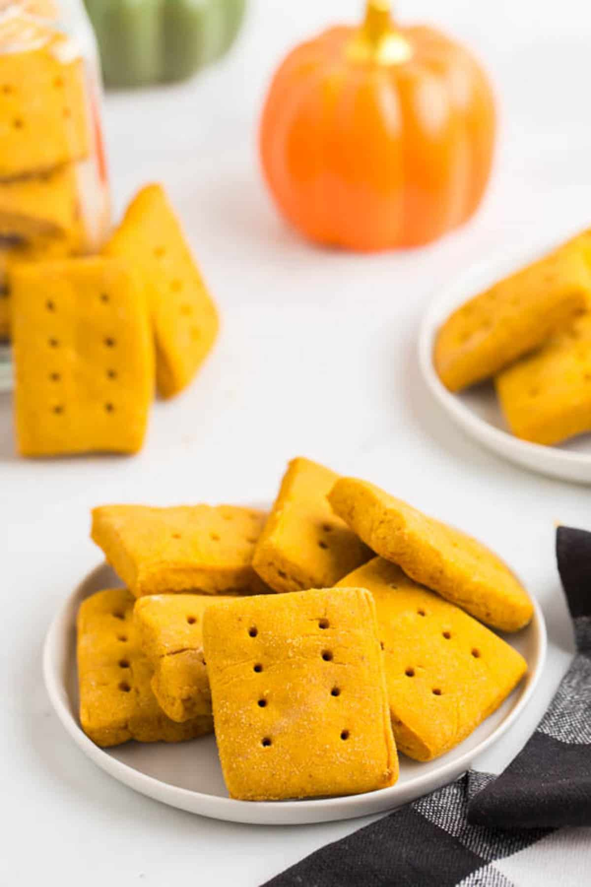 gluten free pumpkin graham crackers stacked on a white plate with more on plates and in a jar in the background