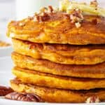 a stack of pumpkin pancakes on a plate topped with a pat of butter, chopped pecans, and maple syrup