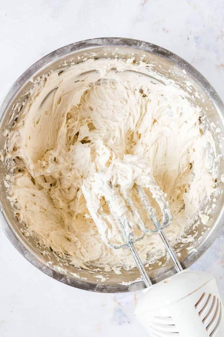 hand mixer set above a bowl of vanilla buttercream frosting