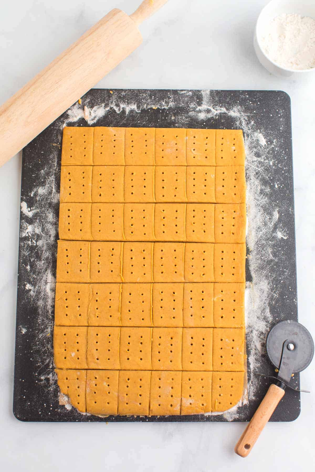 pumpkin cookie dough that has been rolled out and cut into rectangles with small holes poked in each one